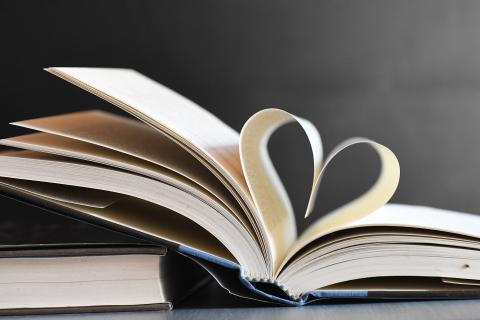 open book with interior pages folded to form a heart